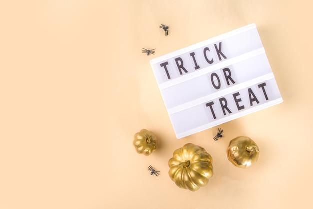 Trick or treat achtergrond, eenvoudige halloween wenskaart, uitnodiging voor feest abstract flatlay met gouden gekleurde pompoenen, sterren, spinnen, op beige gele achtergrond kopie ruimte bovenaanzicht