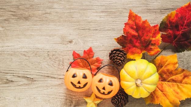 Trick or treat emmers en pompoen in de buurt van bladeren en kegels