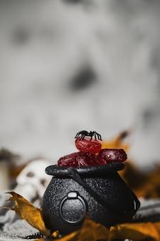 Trick or treat-kaarsen in de ketel voor halloween-schedels op de achtergrond