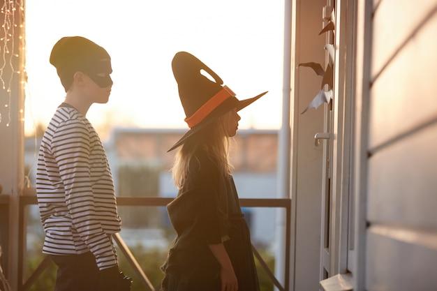Trick or treat kids waiting by door op halloween