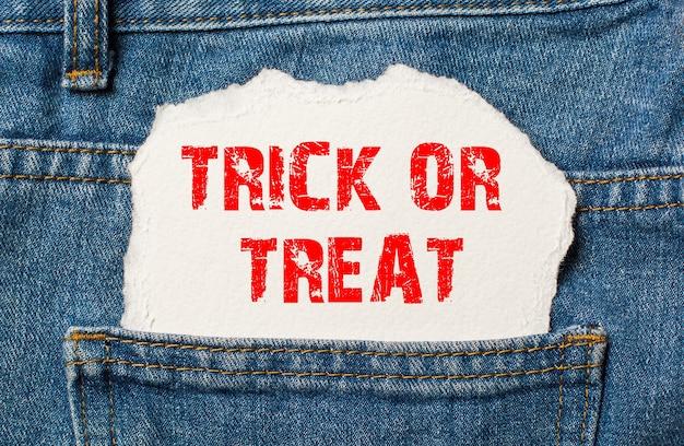 Trick or treat op wit papier in de zak van een blauwe spijkerbroek