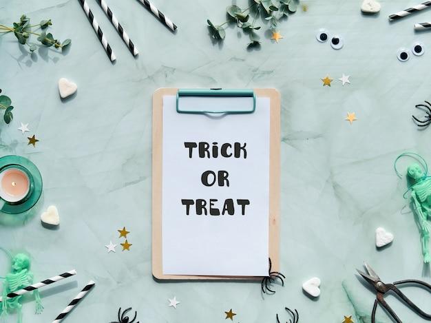 Trick or treat-tekst op mintgroene achtergrond. ecalyptus, theelichtje, kandijsuiker, wiebelogen, spinnen, skeletten, papieren rietjes