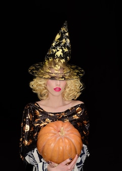 Trick or treat vrouw met pompoen halloween-feest gelukkige halloween blonde vrouw in heksenhoed oktober