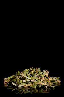 Tricolor instant noodles met spinazie en tomaten op een zwarte achtergrond.