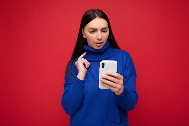 Triest aantrekkelijke goed uitziende jonge brunette vrouw, gekleed in stijlvolle blauwe warme trui in evenwicht geïsoleerd