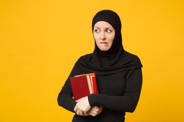 Triest arabische moslim student meisje in hijab zwarte kleding houdt boeken geïsoleerd op gele muur portret. mensen religieuze levensstijl, onderwijs op de middelbare school concept. .