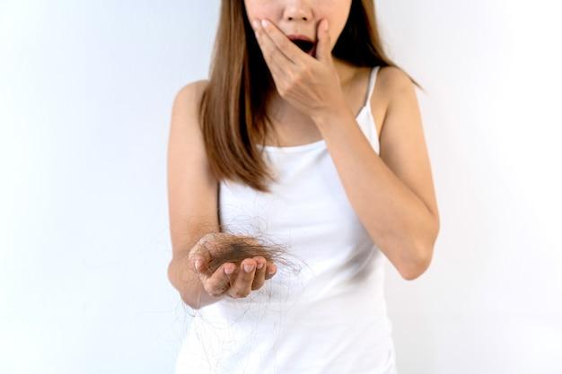 Triest aziatisch meisje kijkt naar haar haaruitval met shock en raakt haar gezicht aan