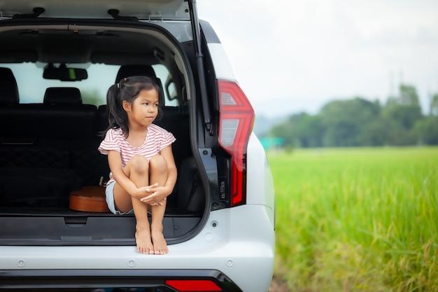 Triest aziatische kind meisje zit alleen in een auto kofferbak en op zoek naar de natuur buiten