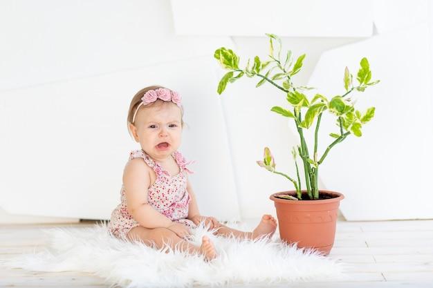 Triest babymeisje zit in een helder witte kamer in een rode jurk met een kamerbloem en huilen
