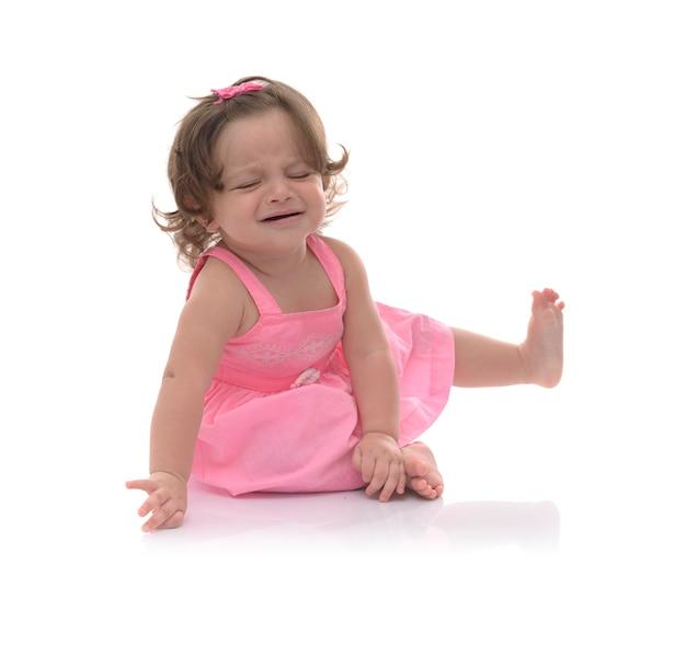 Triest babymeisje zit op witte achtergrond