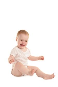 Triest babymeisje zitten en huilen geïsoleerd op een witte achtergrond
