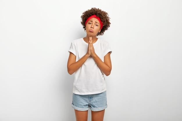 Triest bedelende vrouw met afrohaar houdt handen in gebedgebaar, tuitt lippen en vraagt om enorme gunst, helpt hand in problemen, draagt wit comfortabel t-shirt en korte spijkerbroek, moet zich verontschuldigen