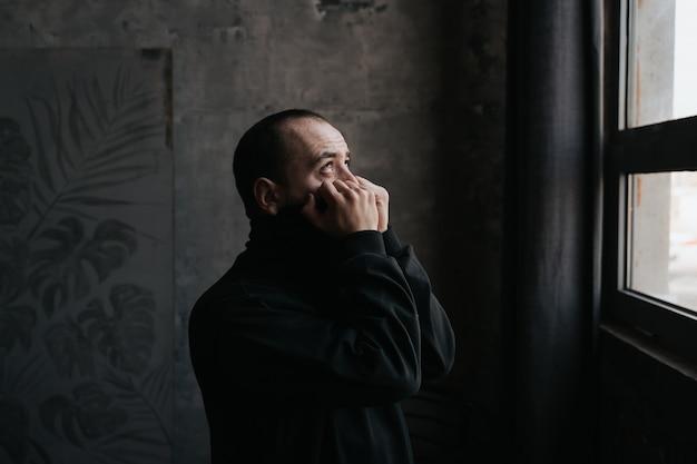 Triest benadrukt jonge bebaarde man alleen. lijdt aan depressie en eenzaamheid, close-up, profielweergave, binnenshuis