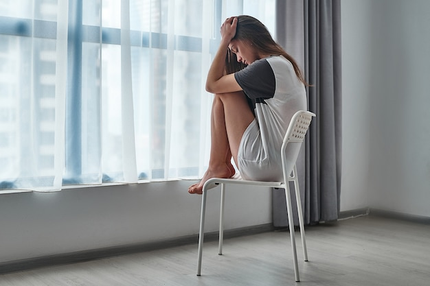 Triest benadrukt ongelukkig depressief melancholische jonge vrouw tiener alleen thuis zitten in de buurt van raam en houdt haar hoofd in haar handen tijdens moeilijkheden leven en depressie
