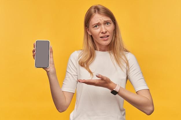 Triest beschaamde vrouw met sproeten in witte t-shirt houden en wijzend op leeg scherm mobiele telefoon op geel
