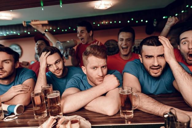 Triest blauwe teamfans bij staaf in bar met rood team.