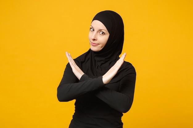 Triest boos huilende verwarde jonge arabische moslimvrouw in hijab zwarte kleding poseren geïsoleerd op gele muur portret. mensen religieuze islam levensstijl concept.