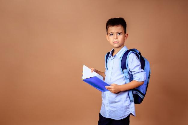 Triest boos jongen schooljongen met een boek in zijn handen op een beige achtergrond