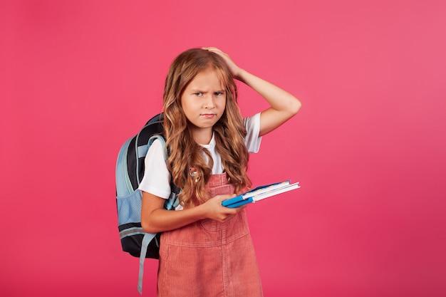 Triest boos meisje schoolmeisje met boeken in haar handen. foto op roze achtergrond