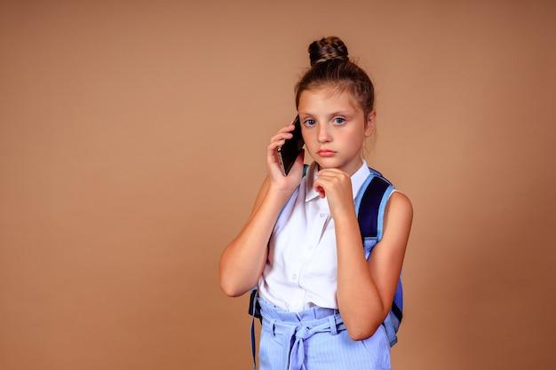 Triest boos schoolmeisje met een telefoon in haar handen