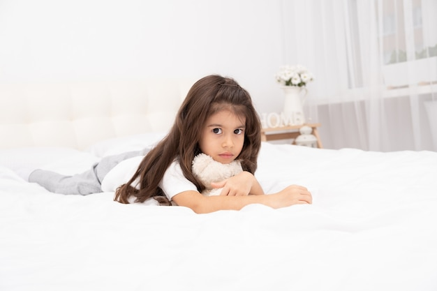 Triest brunette meisje liggend met teddybeer op bed thuis.