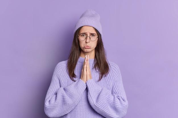 Triest brunette vrouw kijkt met smekende uitdrukking houdt palmen bij elkaar vraagt om verontschuldiging portemonnees lippen draagt ronde bril gekleed in gebreide trui en muts.