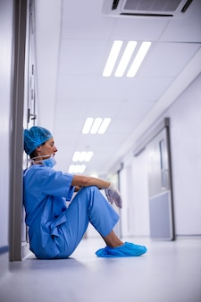 Triest chirurg zittend op de vloer in de gang