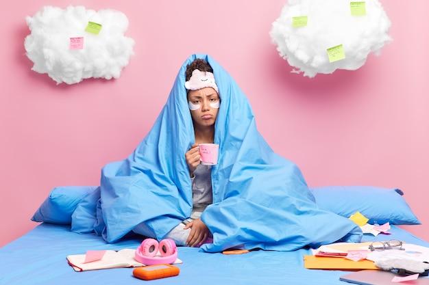 Triest eenzame vrouw gewikkeld in een zachte deken houdt mok koffie met stickers