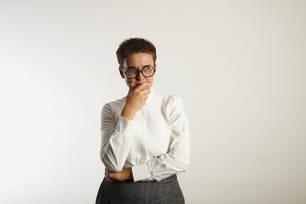 Triest en boos jonge vrouw in witte klassieke blouse en grijze tweed rok na te denken over iets
