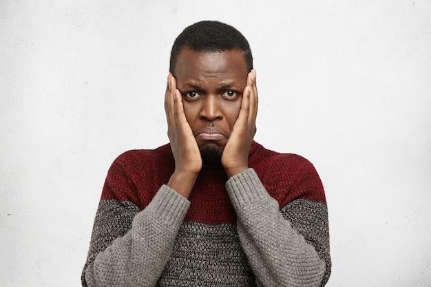 Triest en depressief jonge donkere man hand in hand op de wangen staren met gestreste pijnlijke blik, die lijdt aan slechte kiespijn. menselijke gezichtsuitdrukkingen, emoties en gevoelens