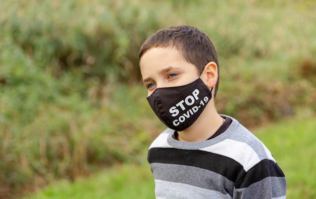 Triest en verveeld schooljongen met gezichtsmasker depressief gevoel