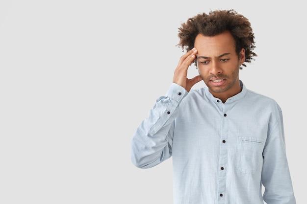 Triest gefrustreerd bezorgd jonge afro-amerikaanse man kijkt neer met peinzende uitdrukking, houdt de hand op het hoofd, probeert het probleem op te lossen, denkt in gedachten, staat tegen een witte muur met kopie ruimte