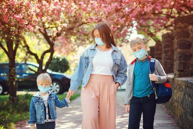 Triest gezin naar huis tijdens quarantaine. familie die gezichtsmaskers in openlucht draagt. lente.