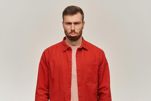 Triest grappige jonge man in rood shirt met baard kijkt beledigd en maakt grappig gezicht over witte muur