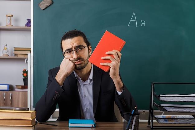 Triest hand op wang mannelijke leraar met een bril die een boek vasthoudt en bekijkt dat aan tafel zit met schoolhulpmiddelen in de klas