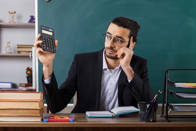 Triest hand op wang mannelijke leraar met een bril die een rekenmachine vasthoudt en bekijkt die aan tafel zit met schoolhulpmiddelen in de klas