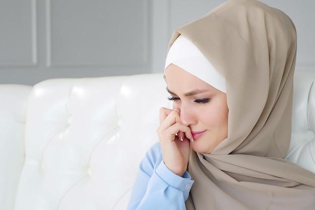 Triest huilende moslimvrouw in hijab zit thuis op de bank.