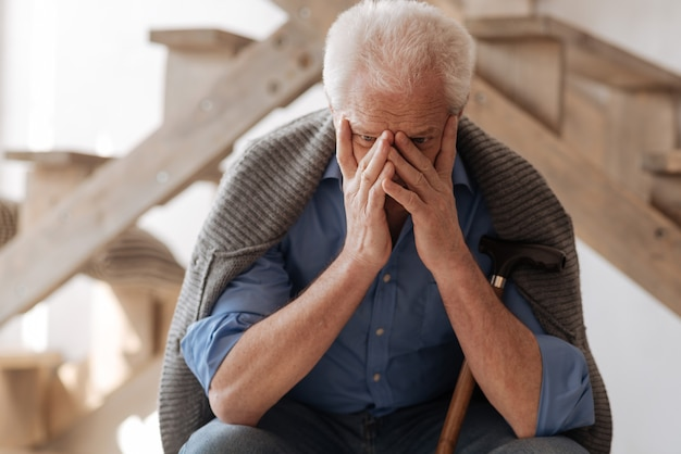 Triest huilende ongelukkige man die zijn gezicht bedekt en huilend terwijl hij rouwde om de persoon van wie hij hield