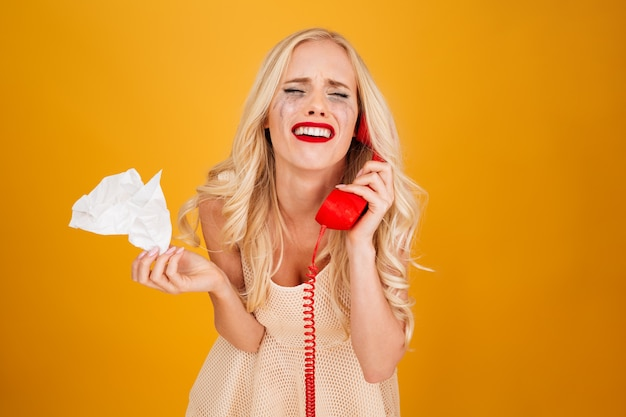 Triest huilende schreeuwende jonge blonde vrouw praten via de telefoon.