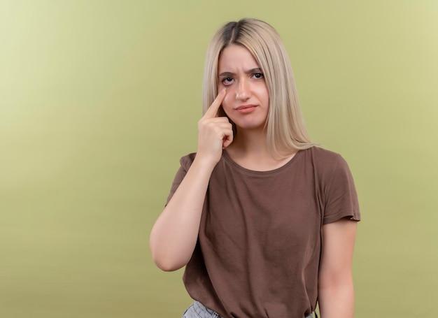 Triest jong blond meisje gebaren huilen met vinger op oog op geïsoleerde groene ruimte met kopie ruimte