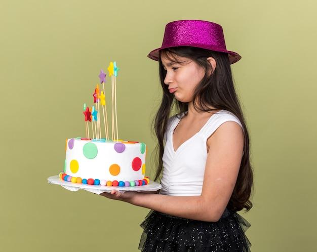 Triest jong kaukasisch meisje met paarse feestmuts die verjaardagstaart vasthoudt en bekijkt, geïsoleerd op olijfgroene muur met kopieerruimte