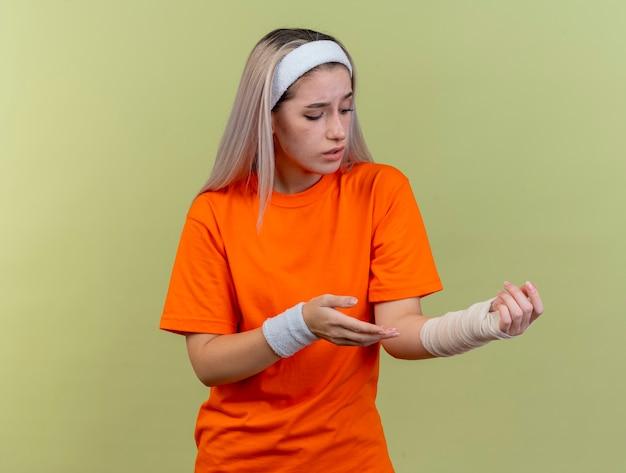 Triest jong kaukasisch sportief meisje met beugels met hoofdband en polsbandjes en kijkt naar de hand