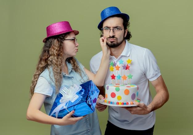 Triest jong koppel met roze en blauwe hoed meisje met geschenkdoos en man wang te houden en man met verjaardagstaart geïsoleerd op olijfgroene muur