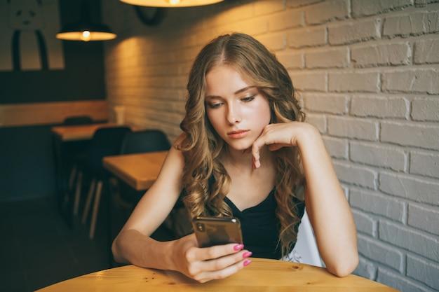Triest jong meisje zit in een café op zoek moe haar telefoon, ongelukkig meisje kijkt naar haar zwarte telefoon,