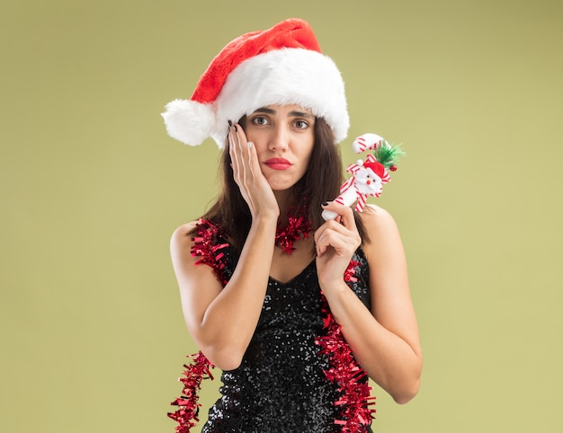 Triest jong mooi meisje met kerstmuts met guirlande op nek met kerstspeelgoed hand op wang geïsoleerd op olijfgroene achtergrond Gratis Foto