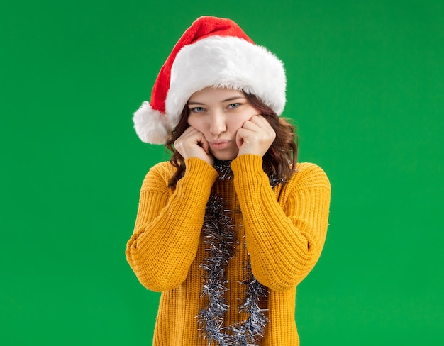 Triest jong slavisch meisje met kerstmuts en met slinger om nek legt handen op gezicht geïsoleerd op groene achtergrond met kopie ruimte