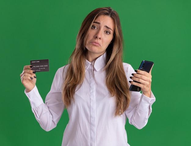 Triest jong, vrij blank meisje houdt creditcard en telefoon geïsoleerd op groene muur met kopieerruimte