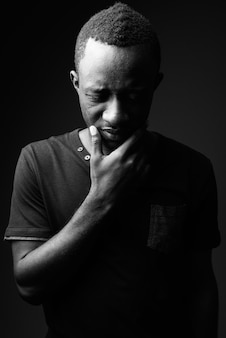 Triest jonge afrikaanse man denken in zwart-wit