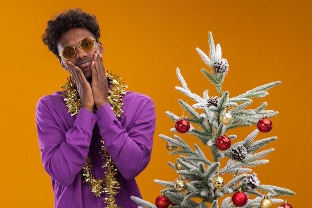 Triest jonge afro-amerikaanse man met bril met klatergoud slinger rond de nek staande in de buurt van versierde kerstboom op een oranje achtergrond