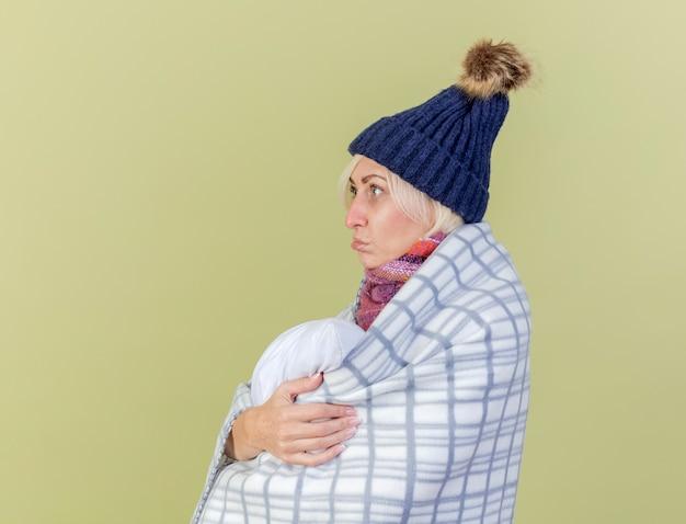 Triest jonge blonde zieke vrouw met muts en sjaal gewikkeld in plaid staat zijwaarts en knuffels kussen geïsoleerd op olijfgroene muur